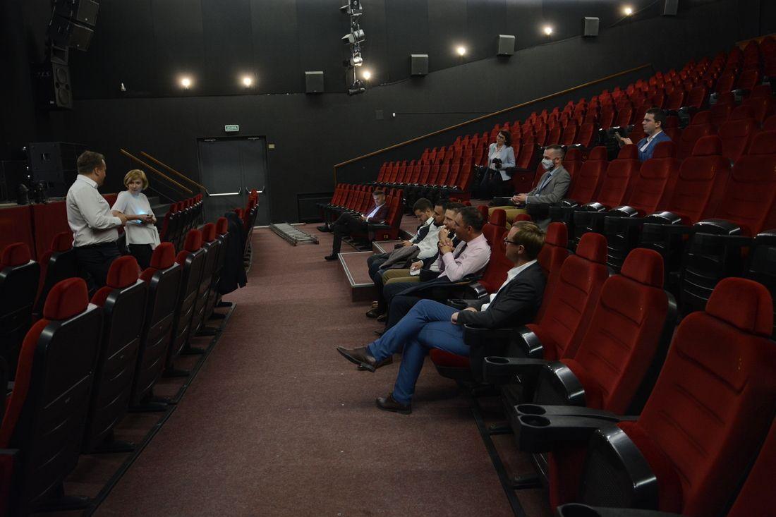 Grupa osób na sali widowiskowej.